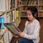 Student reading near the library book shelves